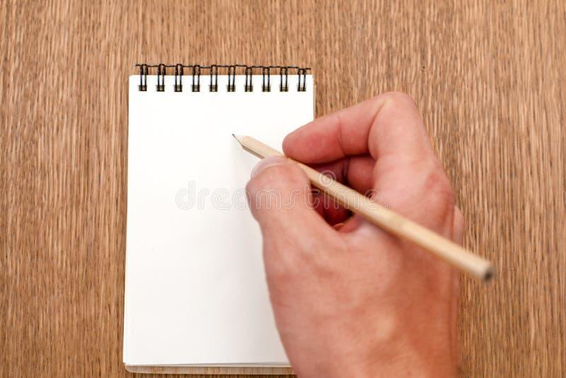 Sauberer Notizblock mit Spirale für Aufschrift- und Schreibenshand mit Bleistift auf hölzernem Hintergrund stockbild