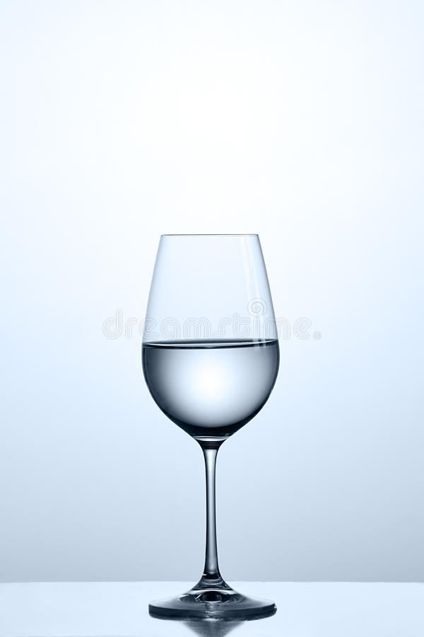 Saubereres Wasser im örtlich festgelegten Weinglas bei der Stellung auf dem sauberen Glas gegen hellen Hintergrund lizenzfreie stockfotos