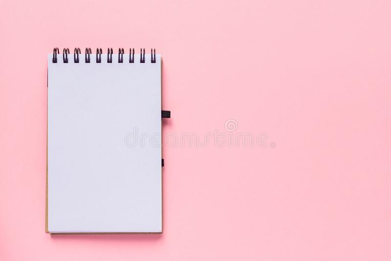 Sauberes gewundenes Anmerkungsbuch für Anmerkungen und Mitteilungen auf rosa Pastellhintergrund Flache Lage des minimalen Geschäf lizenzfreie stockfotos