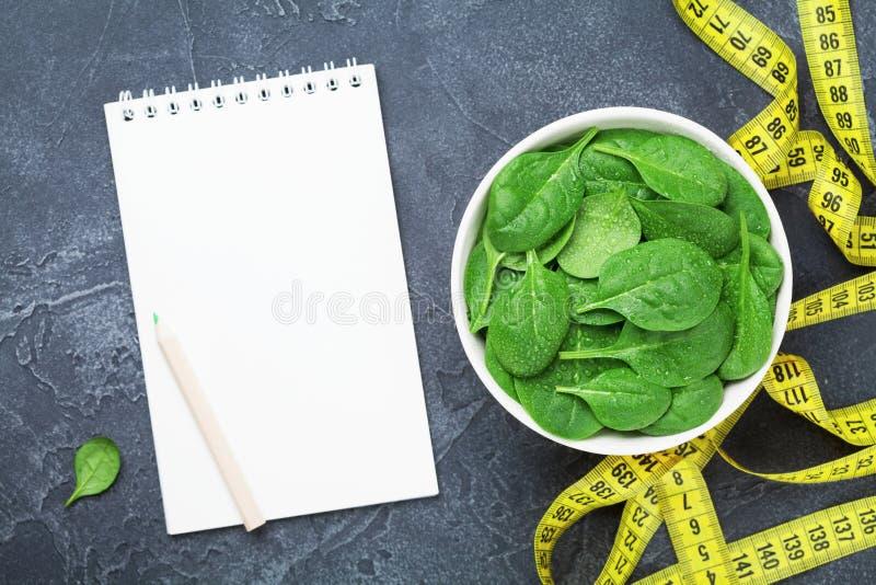 Sauberes Notizbuch, grüne Spinatsblätter und Maßband Draufsicht Diät und gesundes Lebensmittelkonzept stockfotografie