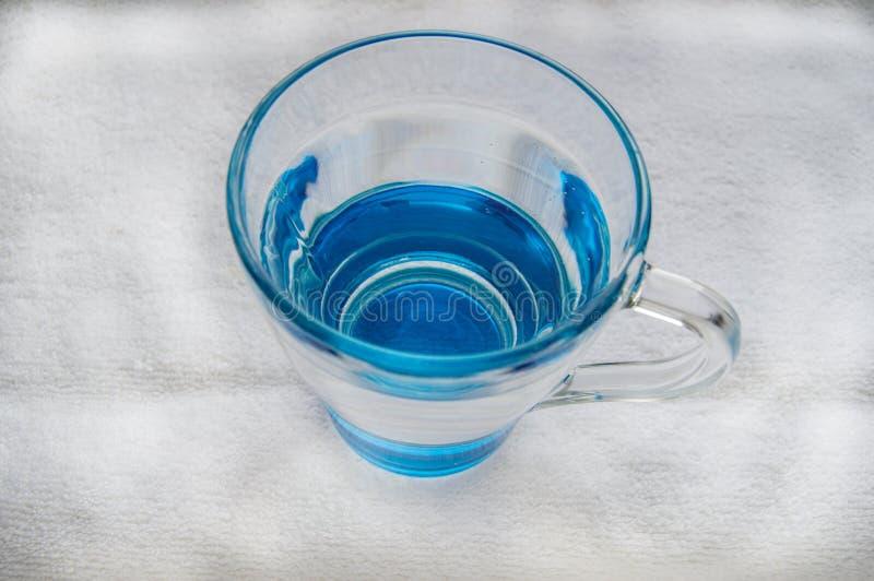 Sauberes Trinkwasser mit Blasen in einem klaren blauen Glas lizenzfreie stockfotos