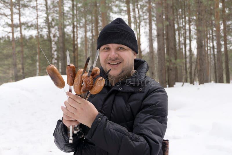 Saucages auf Aufsteckspindeln in den Händen eines Mannes lizenzfreie stockfotografie