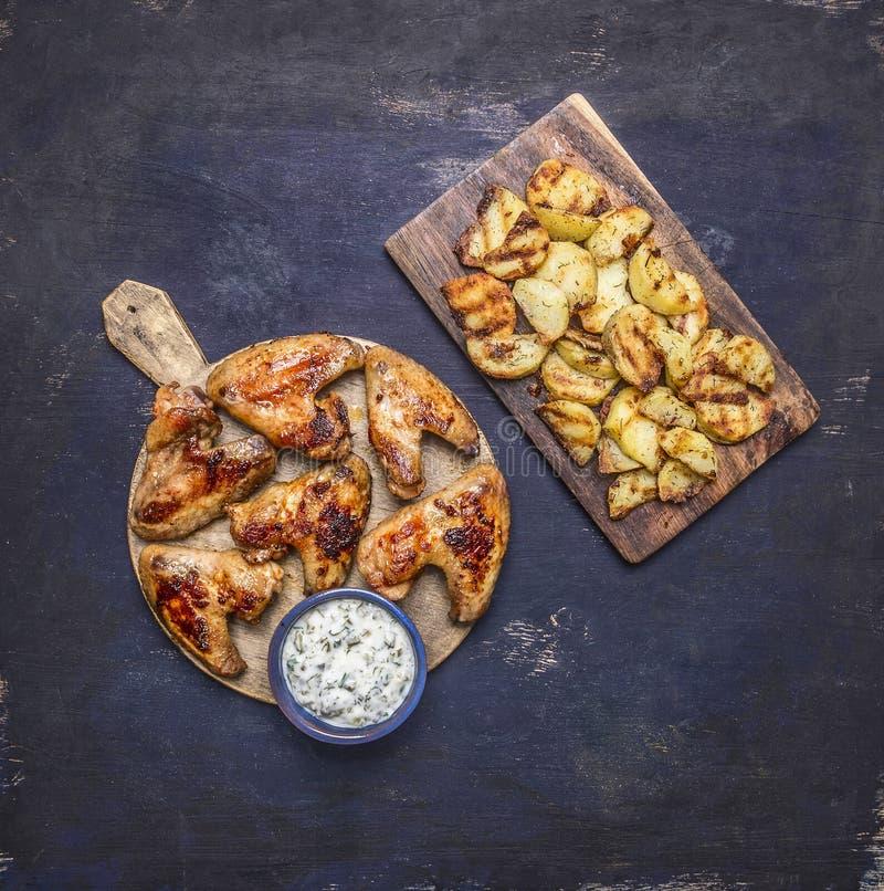 Sauce à ail grillée délicieuse d'ailes de poulet et pommes de terre frites avec l'aneth sur la fin rustique en bois de vue supéri photo stock