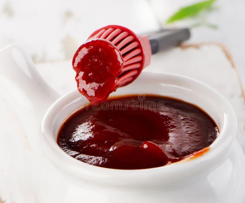 Sauce à BBQ dans la cuvette avec une brosse photographie stock libre de droits