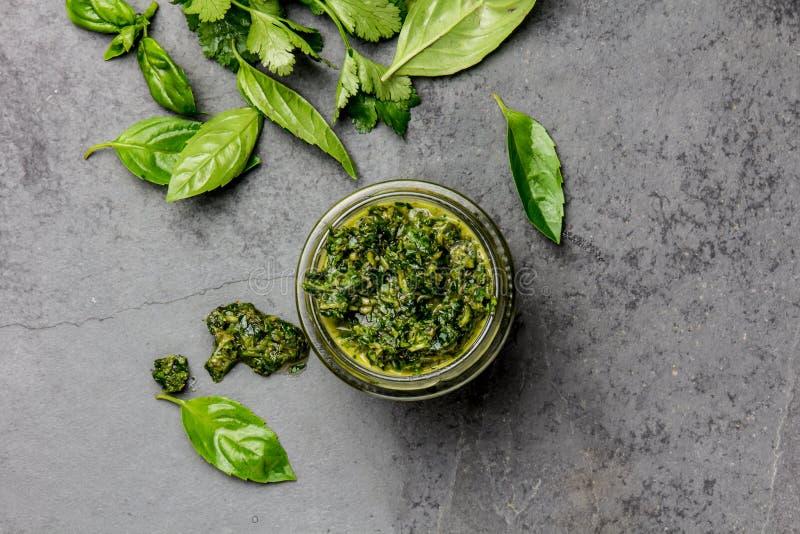 Sauce à Chimichurri Chimichurri vert argentin de sauce à basilic de persil pour l'asado de barbecue dans le pot en verre, ardoise images stock
