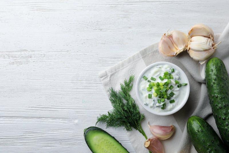 Sauce à concombre de Tzatziki avec des ingrédients sur le fond en bois, vue supérieure photo stock
