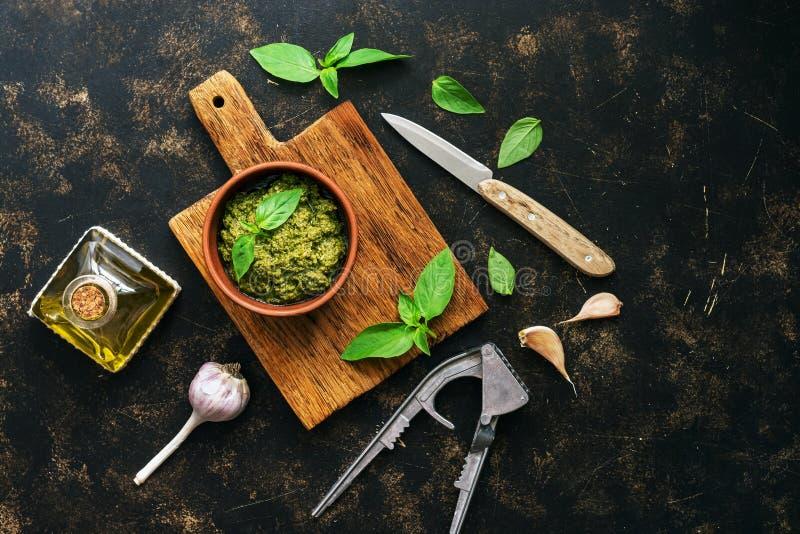 Sauce à pesto en cuvette d'argile, feuilles de basilic et ail sur un fond foncé, vue supérieure Sauce savoureuse méditerranéenne photo libre de droits