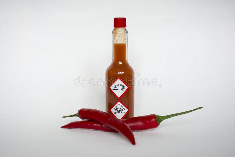 Sauce à piments avec les étiquettes de mise en garde chimiques de risque images stock