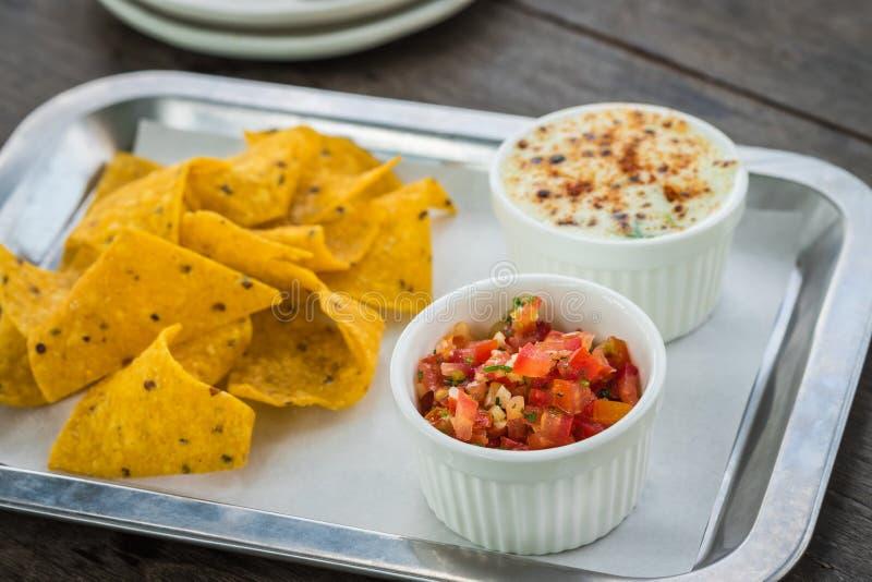 Sauce à Salsa avec des puces de nacho et épinards cuits au four avec du fromage photos libres de droits