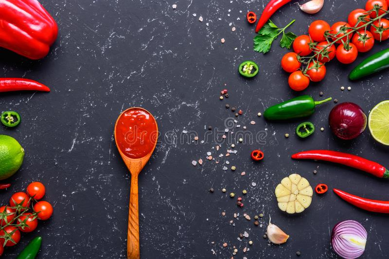 Sauce à Salsa en cuillère et ingrédients en bois sur la table en pierre noire Sauce tomate faite maison Vue supérieure avec l'esp photos stock