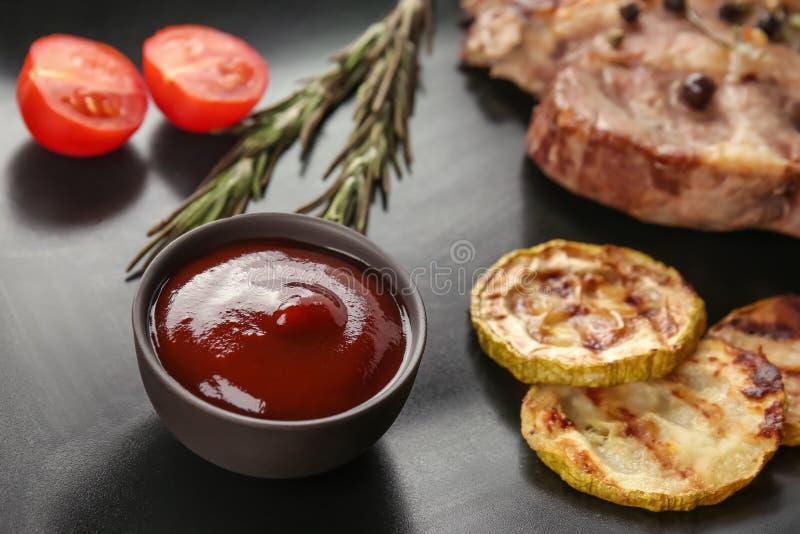 Sauce barbecue délicieuse dans la cuvette avec de la viande et les légumes grillés sur le fond noir photographie stock libre de droits