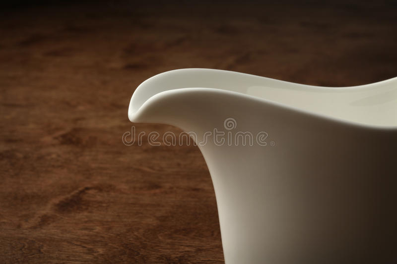 Sauce boat. Detail of a sauce boat on a wooden table stock photos