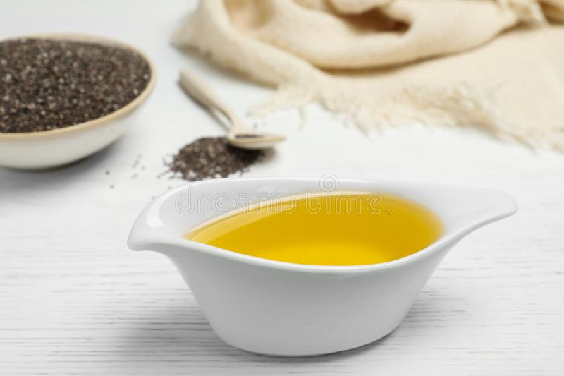 Sauce boat with chia seed oil. On table royalty free stock image