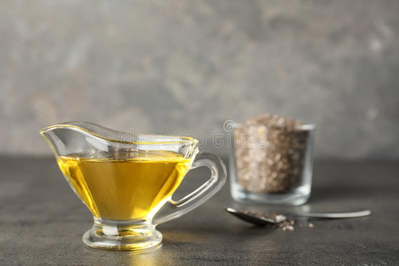 Sauce boat with chia seeds oil on grey table. Space for text royalty free stock photo
