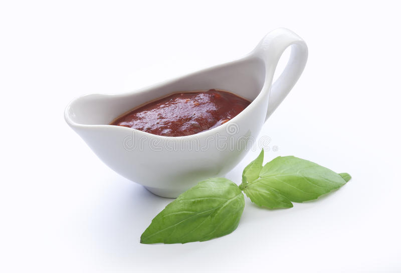 Sauce-boat. Red tomato sauce in the sauce-boat with green basil royalty free stock photo