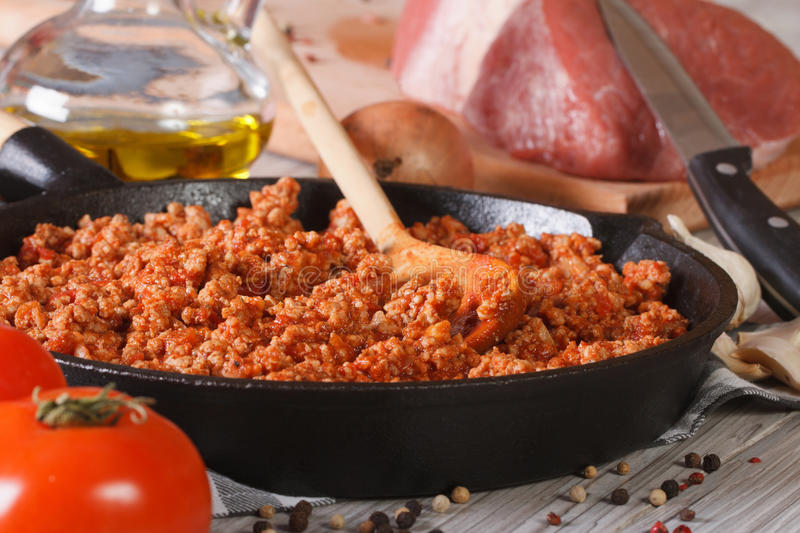 Sauce Bolognese in a pan and ingredients closeup horizontal. Hot sauce Bolognese in a frying pan and fresh ingredients close-up on the table. horizontal royalty free stock photo