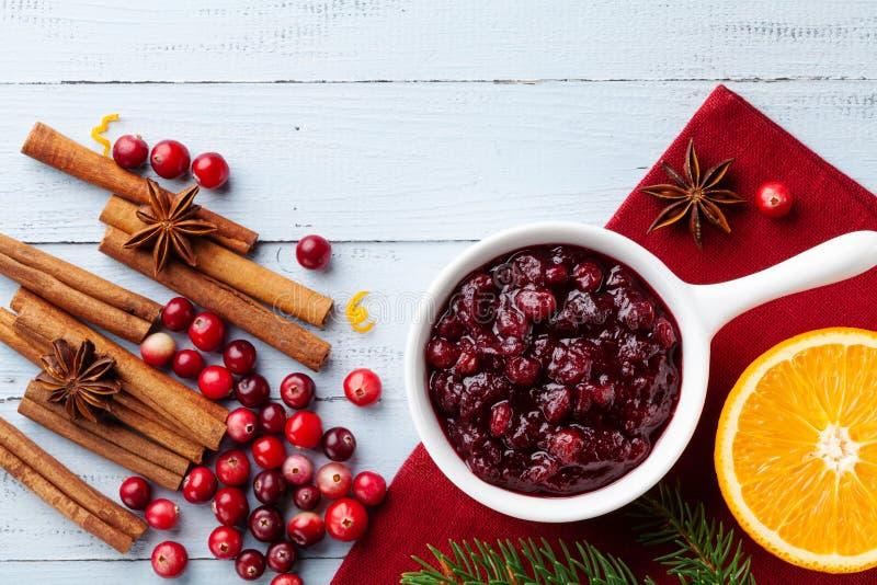 Sauce canneberge dans une casserole en céramique avec ingrédients pour la cuisine décorée de sapin pour Noël ou le jour de l'Acti images stock