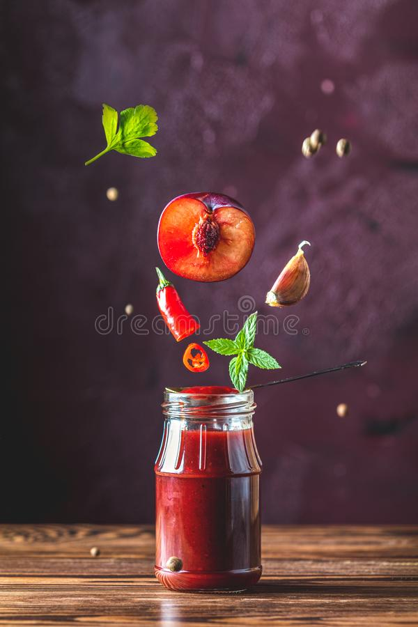 Sauce components frozen in the air. Homemade plum sauce chutney with chilli or tkemali in glass jar standing on wooden table with stock image