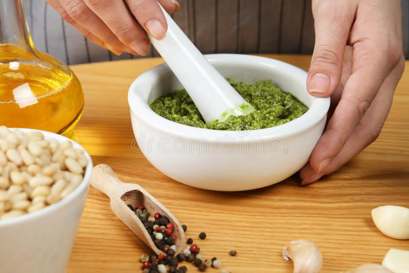 Sauce de mélange à pesto de femme avec le pilon en mortier à la table photos stock