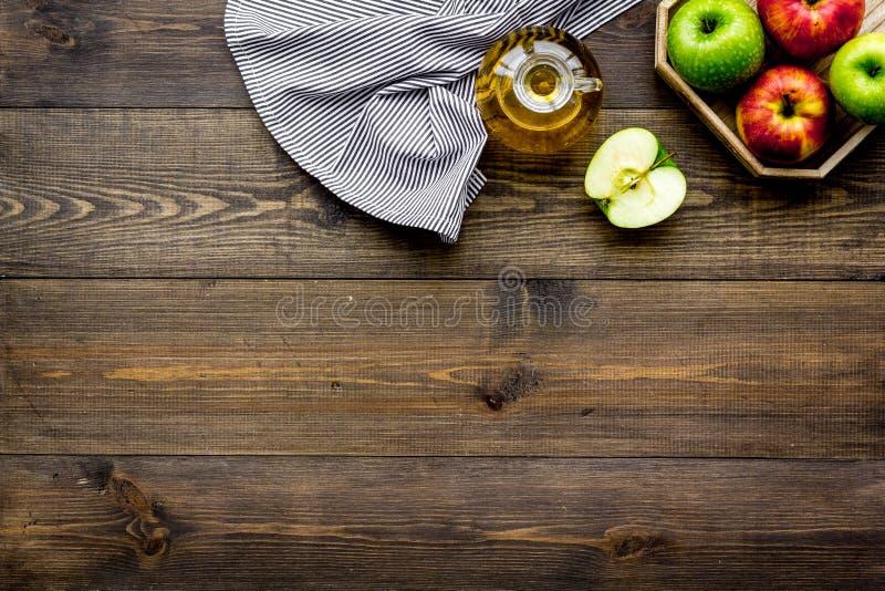 Sauce légère à salade Vinaigre de cidre d'Apple dans la bouteille parmi les pommes fraîches sur l'espace en bois foncé de copie d photo stock
