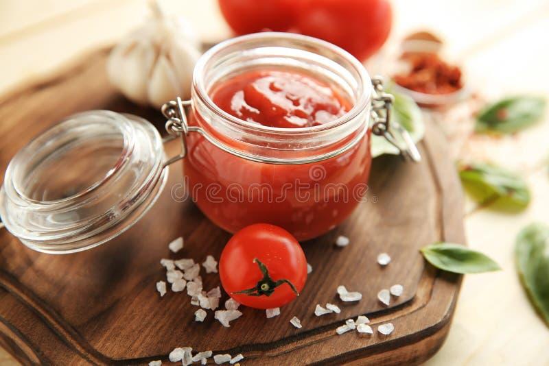 Sauce rouge délicieuse dans le pot en verre sur le panneau en bois, plan rapproché photos stock
