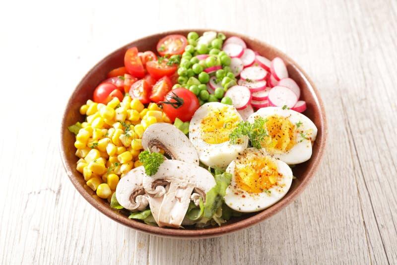 Sauce salade à la tomate, aux oeufs, au maïs, au radis et au pois photographie stock