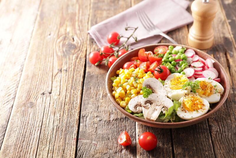 Sauce salade à la tomate, aux oeufs, au maïs, au radis et au pois photographie stock libre de droits