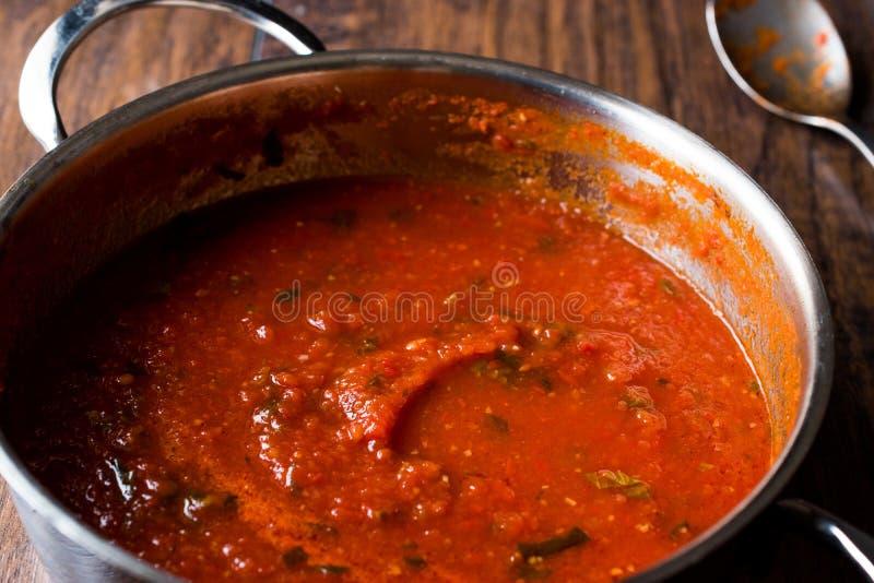 Sauce tomate avec des herbes dans le pot en métal photo stock