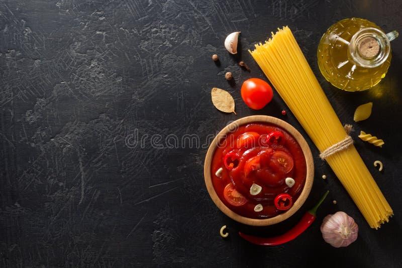 Sauce tomate dans la cuvette sur le fond noir photo stock