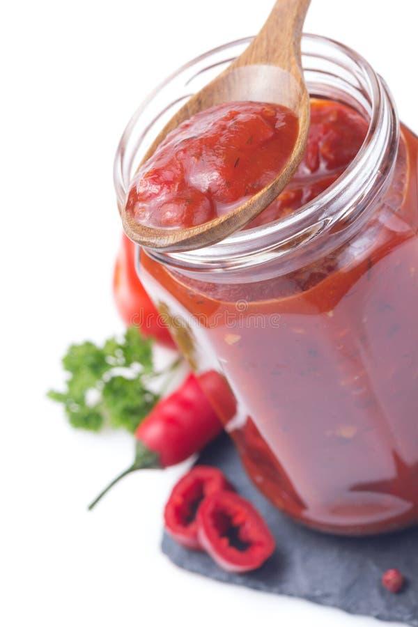 Sauce tomate dans le pot en verre sur le blanc photo libre de droits