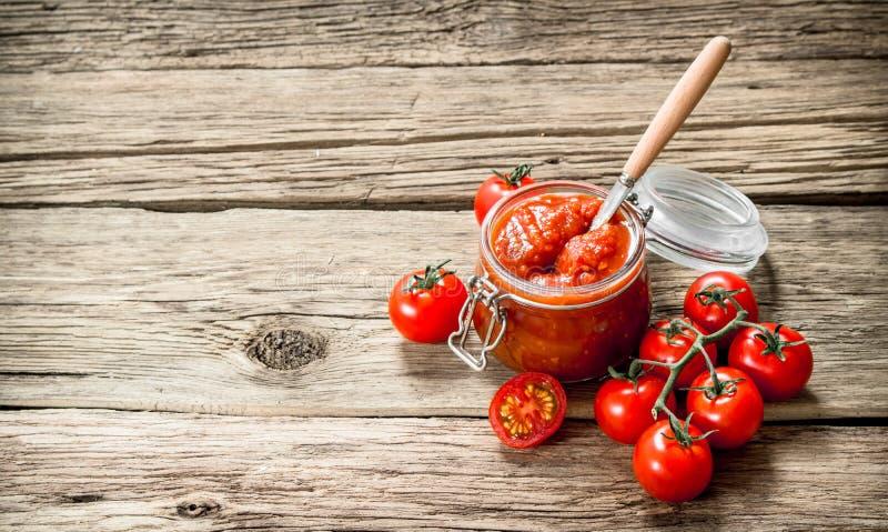 Sauce tomate dans un pot en verre avec les tomates fraîches images stock