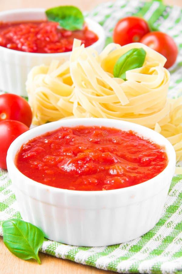 Sauce tomate italienne dans une tasse blanche avec les pâtes, le basilic et le ch crus photographie stock libre de droits