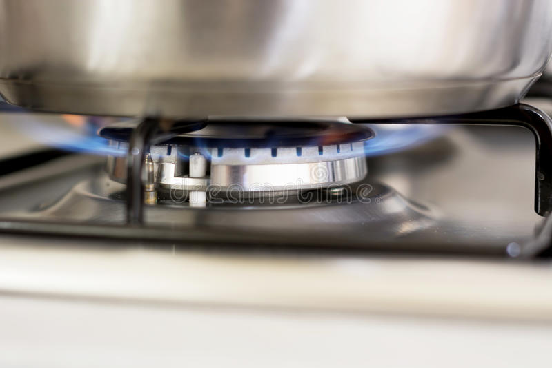 Saucepan on burning gas. In hearth ring of kitchen stove stock image