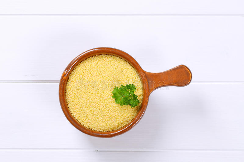 Saucepan of raw couscous. On white wooden background stock photo