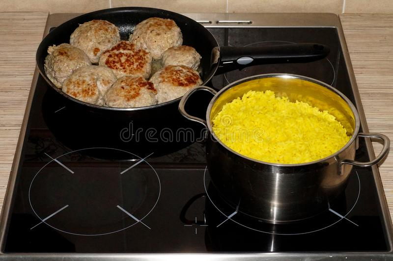 A saucepan of rice and a frying pan with cutlets. A saucepan of rice and a frying pan with cutlets is prepared on the stove stock photography