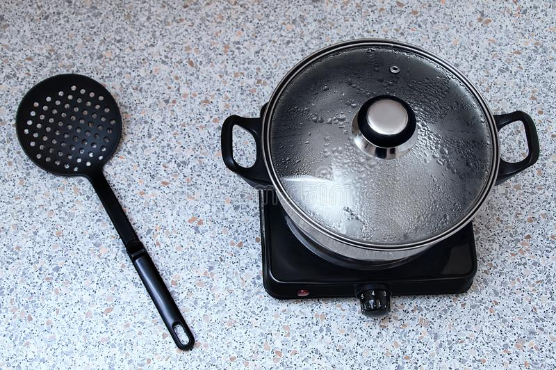 Saucepan on a small electric stove with a lid for a couple. On the table is a plastic black skimmer spoon. View from above stock images
