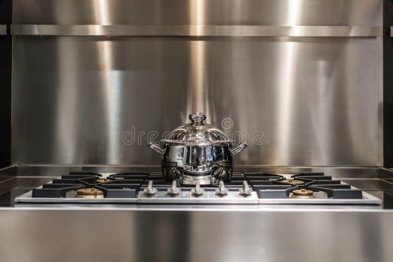 Saucepan on stove. New stainless steel saucepan on modern kitchen range stock photos