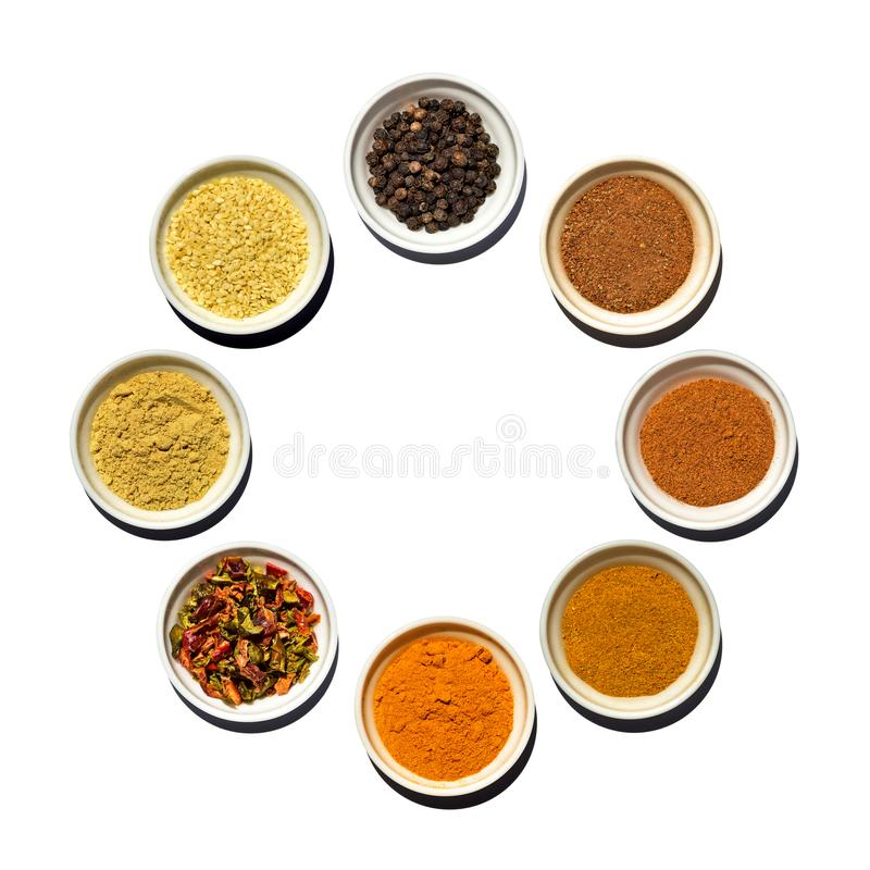 Saucer`s dish with black pepper peas, cinnamon, red pepper, curry, turmeric, granulated dried sweet pepper, mustard, sesame seeds stock photo
