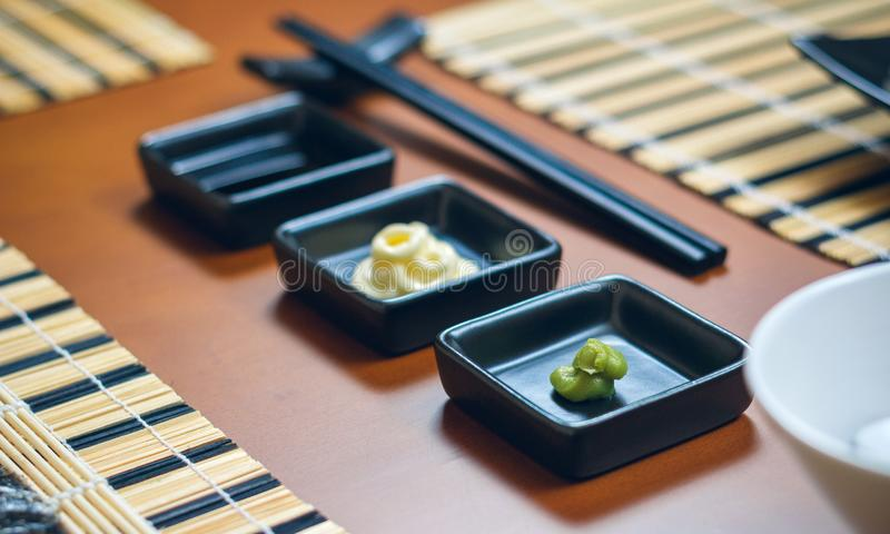 Saucers with wasabi, mayonnaise and soy sauce royalty free stock photography