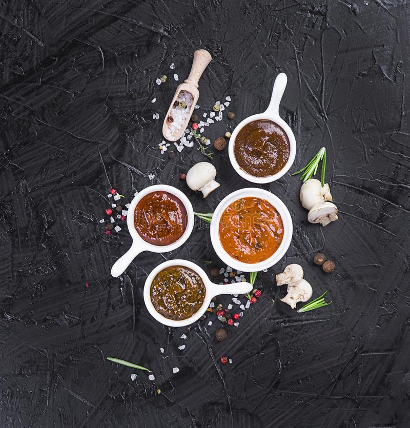 Free Sauces In Cups On A Black Background. Different Sauces Of Red And Orange Color On A Black Stone Board With Spices Stock Photography - 144921852