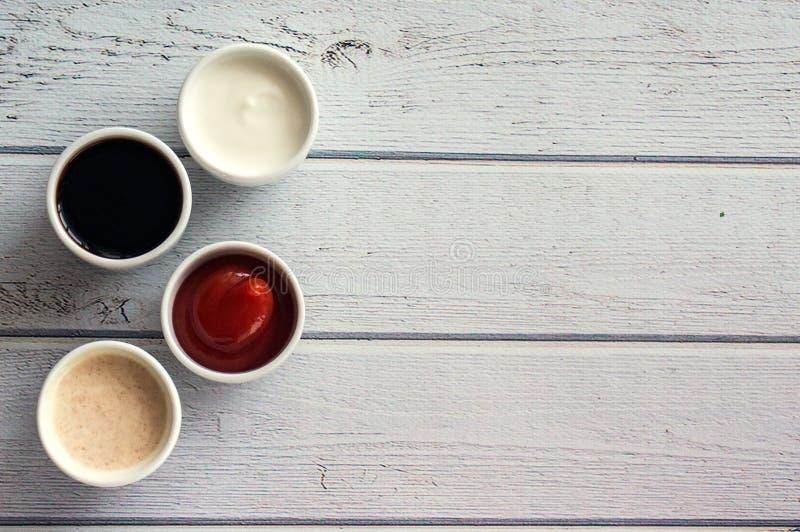 Sauces Ketschup, Senf, Majonäse, Sauerrahm, Sojasoße in den Lehmschüsseln auf hölzernem weißem Hintergrund stockfotos