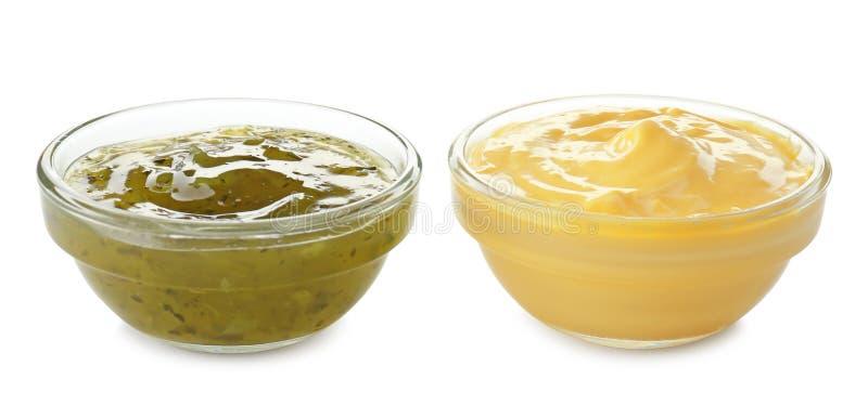 Sauces savoureuses dans des cuvettes sur le fond blanc photos stock