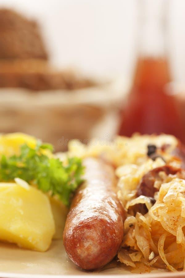 Saucisse avec les pommes de terre et la choucroute image stock