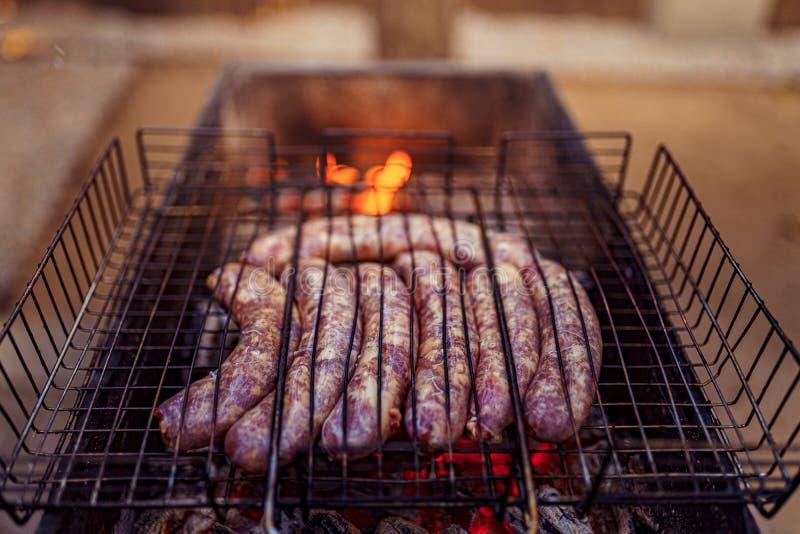 Saucisse crue grillée sur le gril de flamber de pique-nique photographie stock libre de droits