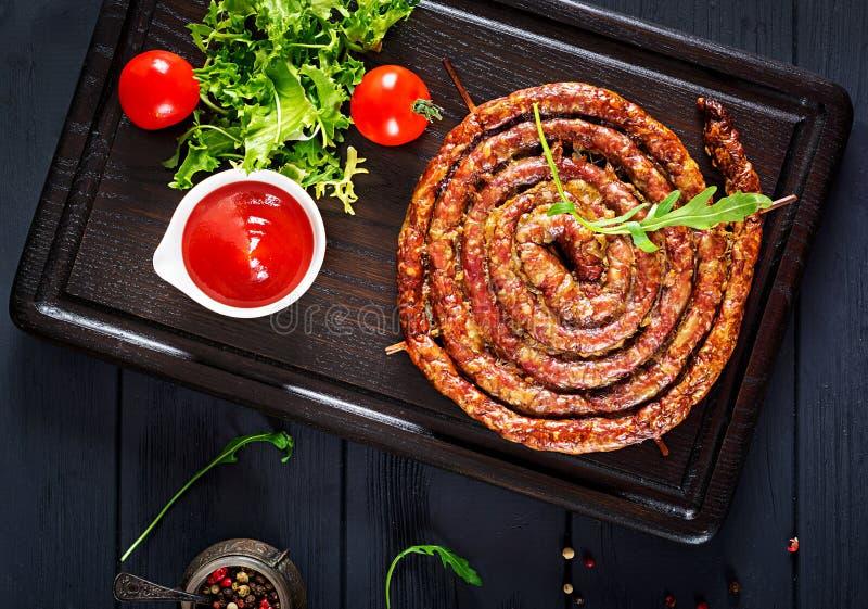 Saucisse faite maison cuite au four sur un conseil en bois images libres de droits