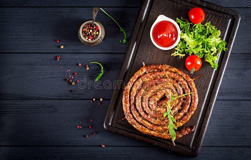 Saucisse faite maison cuite au four sur un conseil en bois image stock