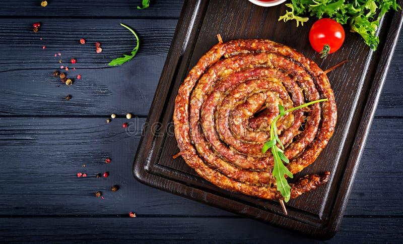 Saucisse faite maison cuite au four sur un conseil en bois photos libres de droits