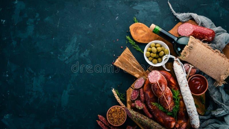Saucisse Fuet, salami, carton sur le panneau de cuisine Sur un fond noir image stock