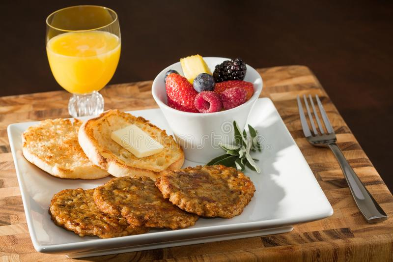 Saucisse Patty Breakfast avec le petit pain anglais, le fruit frais et le jus image stock