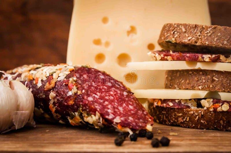 Saucisse sèche et fromage avec des trous pour le petit déjeuner images libres de droits
